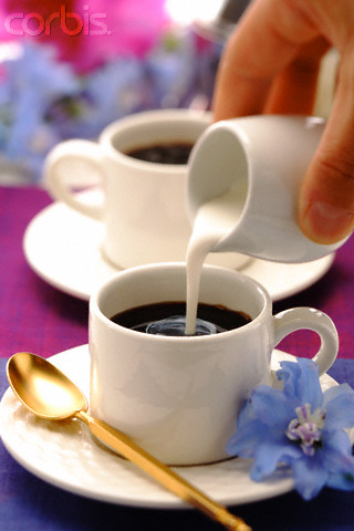 Hand Pouring Cream into Coffee Cup