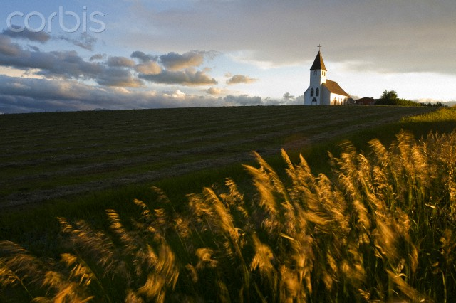 Sunset over hay field and St Mary's church near Pincher Creek, Alberta, Canada.