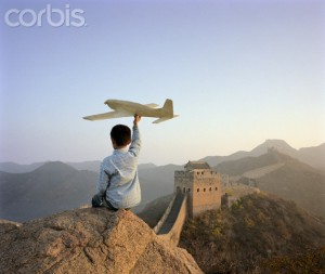 Boy holding paper plane on Jinshanling Great Wall