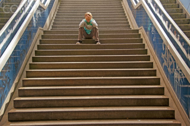 Lonely boy sitting on a staircase, Cologne, Rhineland, North Rhine-Westphalia, Germany, Europe