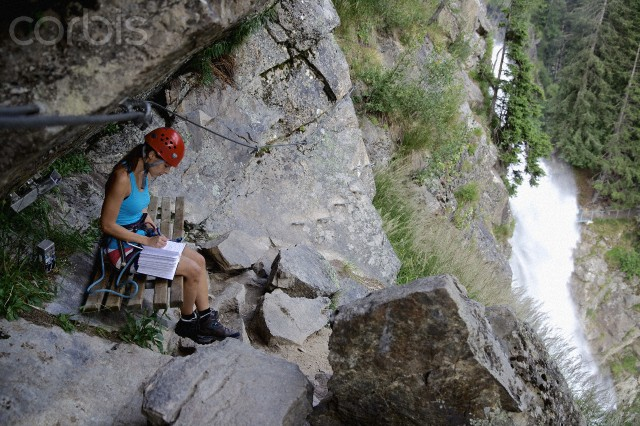 Female climber reading book in rock crevice